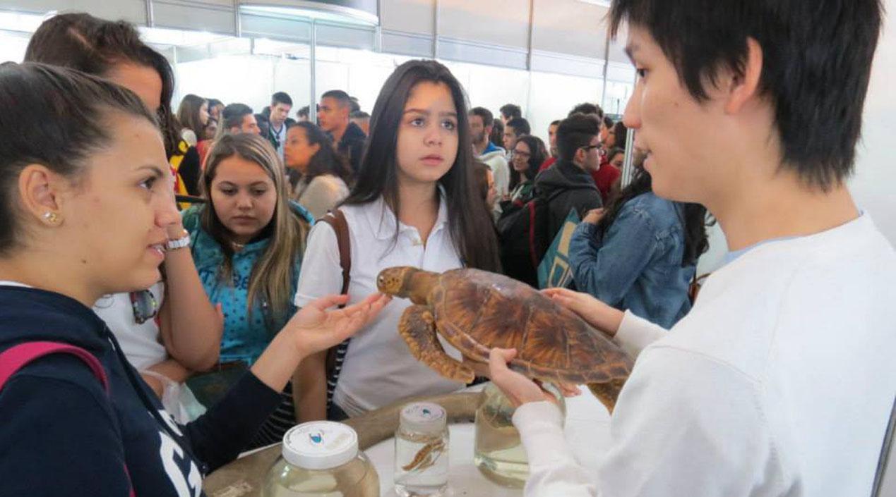 Visitantes da Feira de Profissões conversando com professor no estande da Faculdade de Odontologia de Bauru